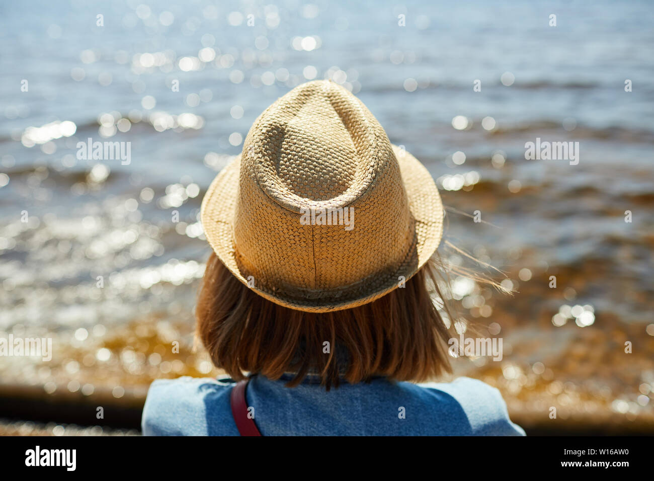 Back view portrait of young woman wearing straw hat looking out at sea in Summer, copy space Stock Photo