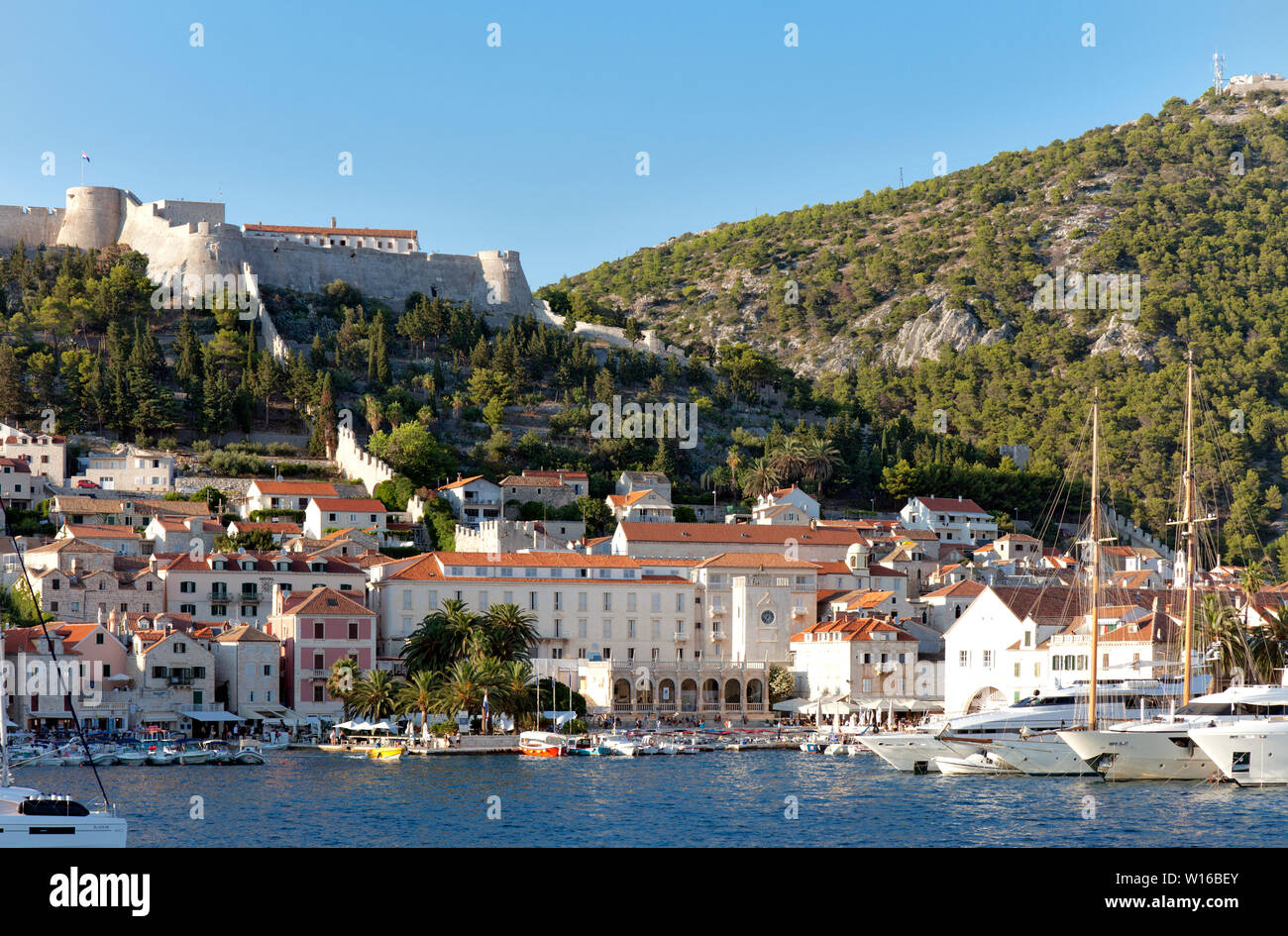 Hvar Town and its harbor as seen from a sea approach.  This Adriatic playground attracts celebrities and mega-yachts. Stock Photo