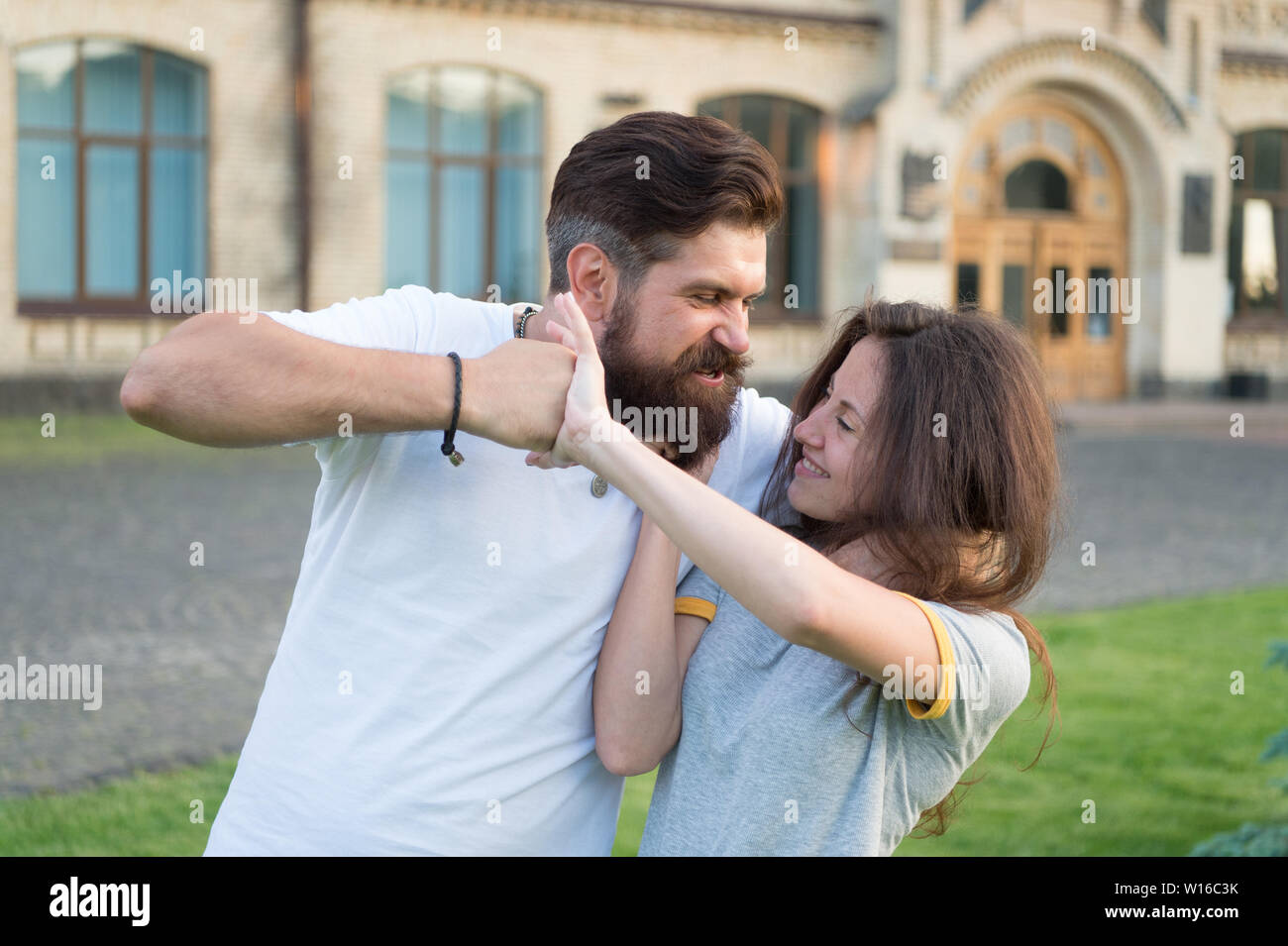 Taking a lot of abuse from him. Bearded man pushing girl using physical abuse in public. Woman experiencing violence and abuse. Domestic violence as a gender-based form of extreme human rights abuse. - Stock Image