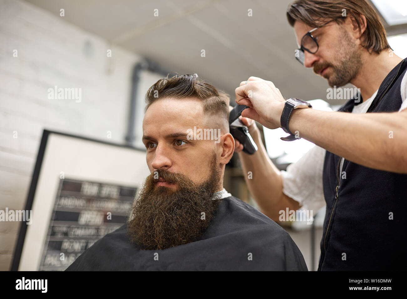Brutal guy in modern Barber Shop. Hairdresser makes hairstyle a man with a long beard. Master hairdresser does hairstyle with hair clipper Stock Photo