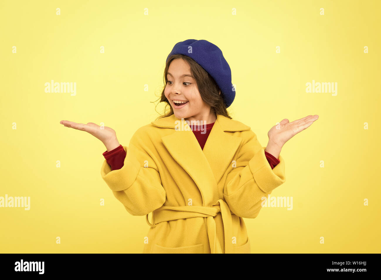 Child promoting something yellow background copy space. Place for ad advertisement. Girl show open palm. Advertising product. Look at this. Advertisement launching product. Advertisement concept. - Stock Image