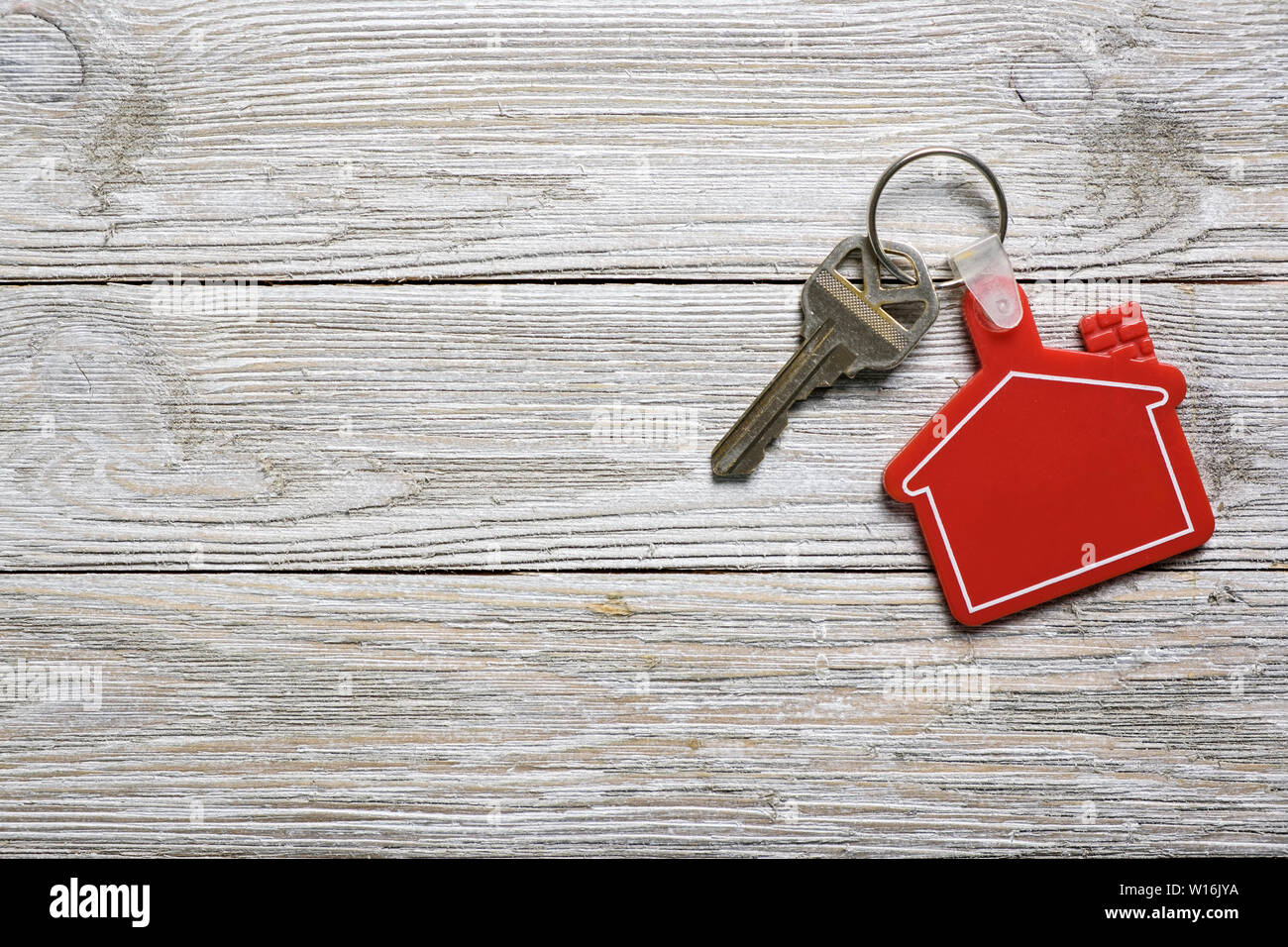 House key with red house shape keychain for real estate concept - Stock Image