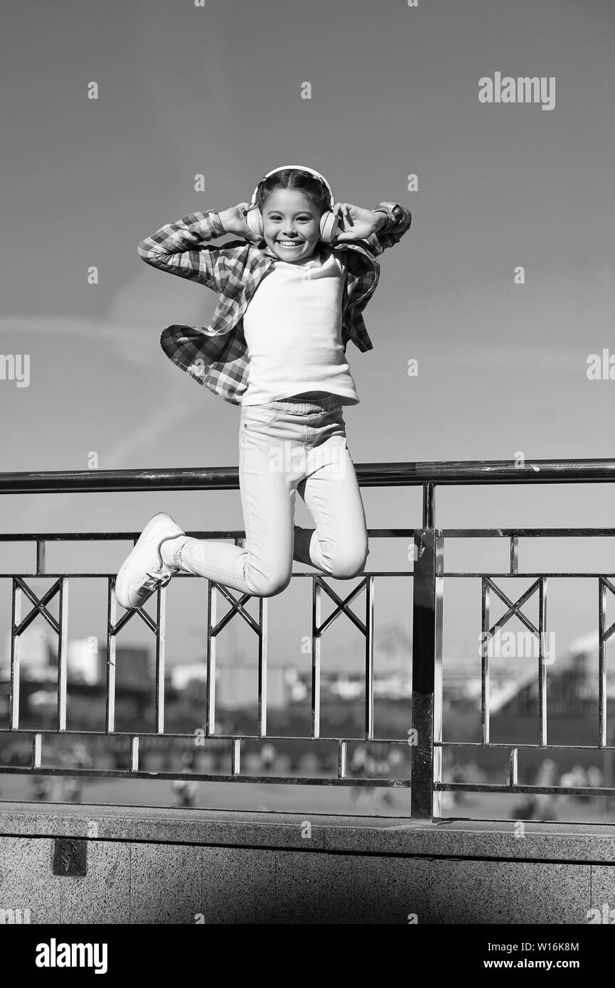 5903dc4b Little girl jumping to music. Small happy child listening to