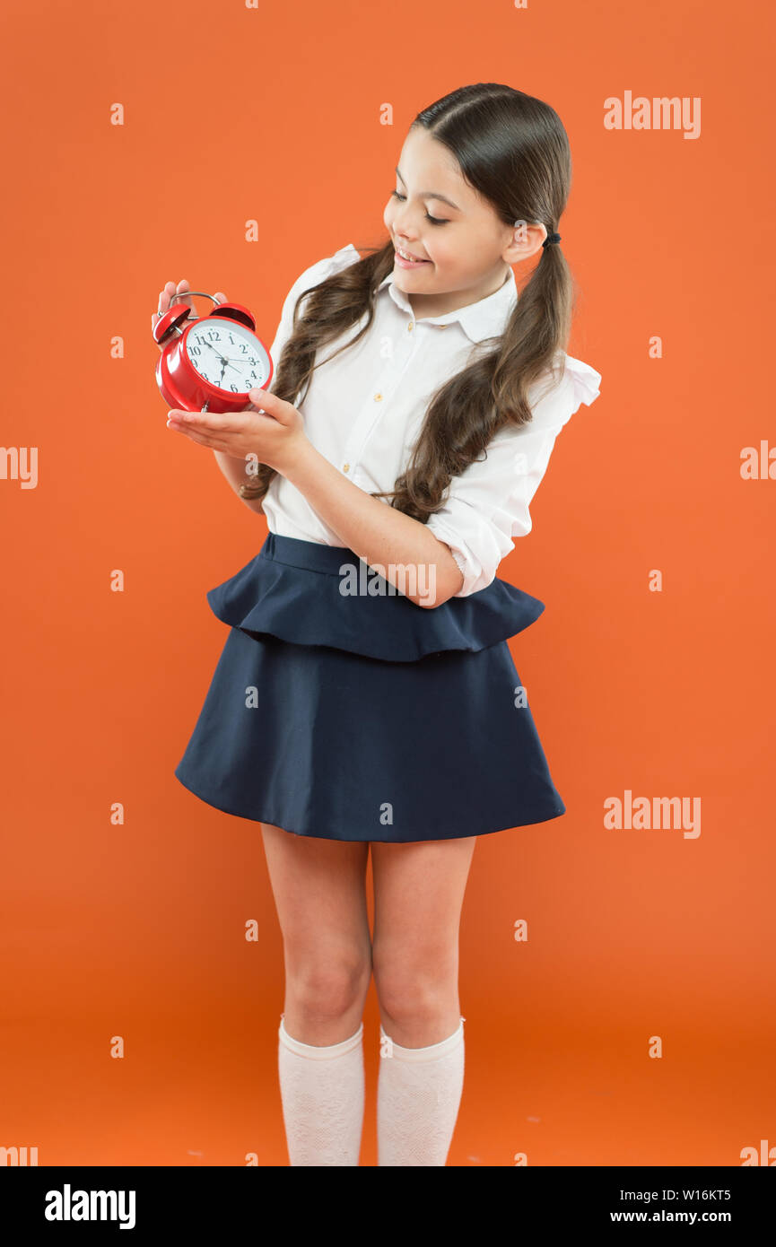 School time. Children education. Knowledge day. time to go to school. Happy girl hold alarm clock counting for lunch time. daily routine schedule. schoolgirl and retro alarm clock. Back to school. Stock Photo