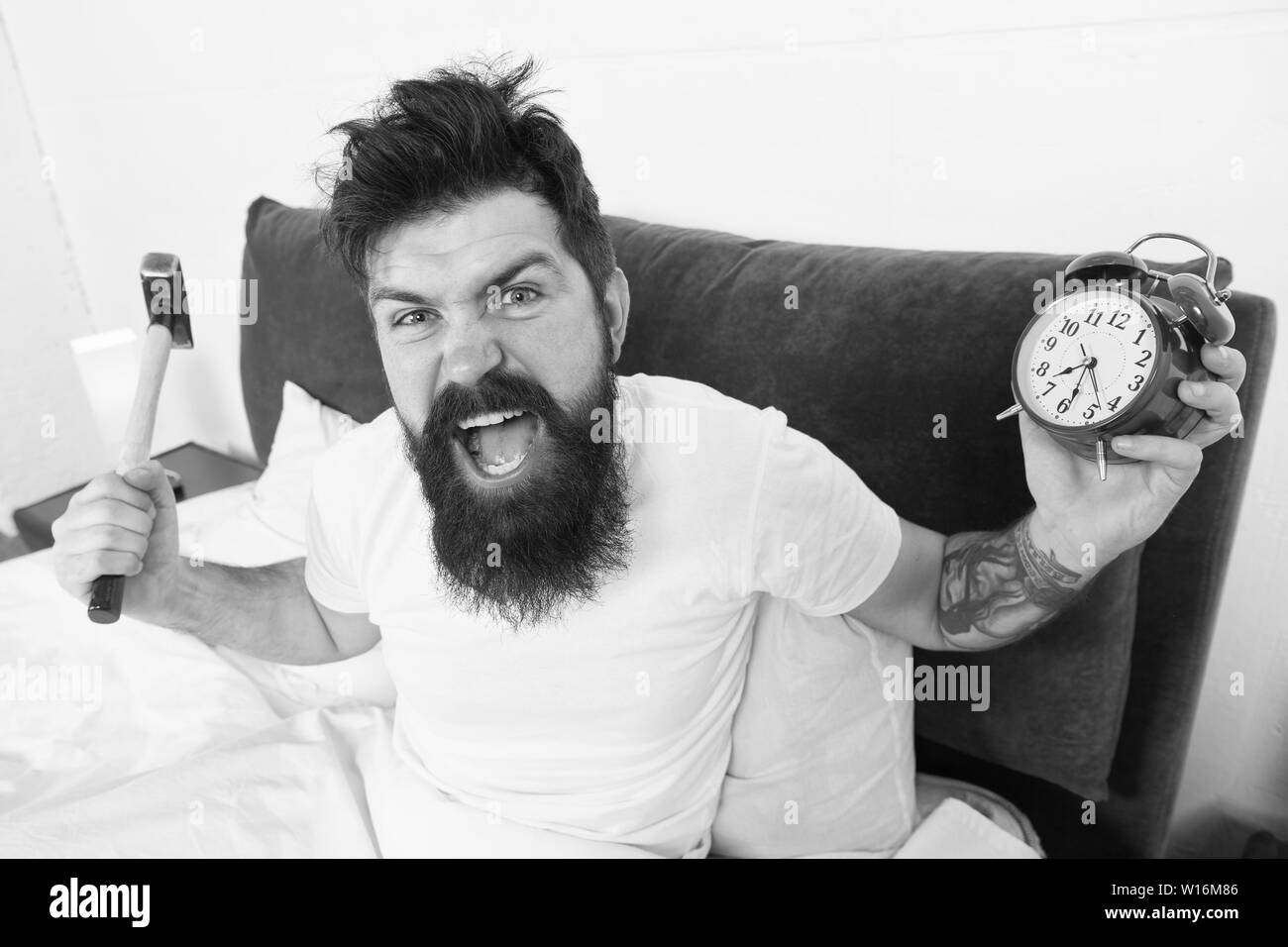 Tips for waking up early. Tips for becoming an early riser. Man bearded hipster sleepy face in bed with alarm clock. Problem with early morning awakening. Get up with alarm clock. Overslept again. - Stock Image