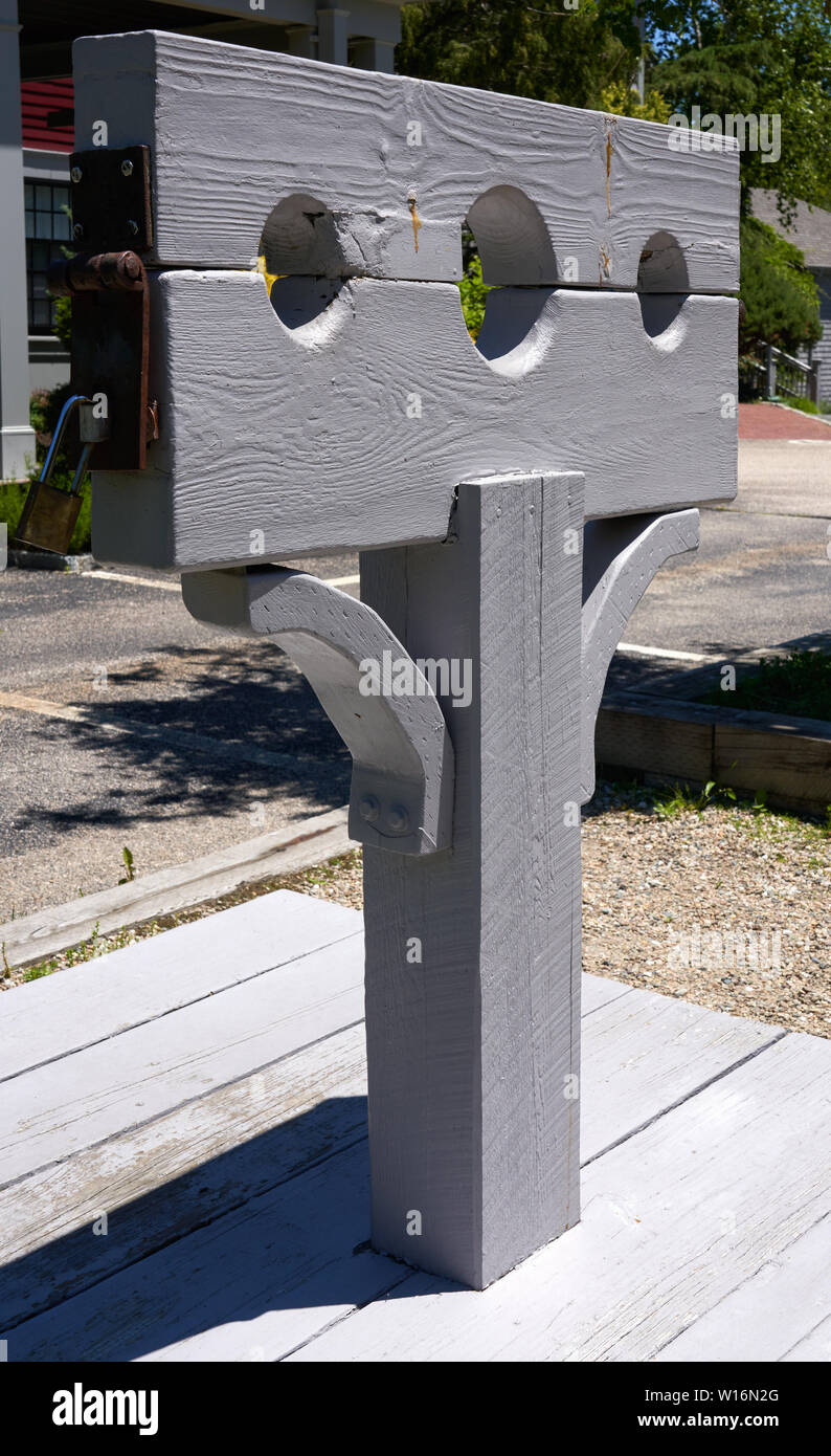 grey wooden post with pillory or stocks used for restraint of a person for punishment and public humiliation Stock Photo