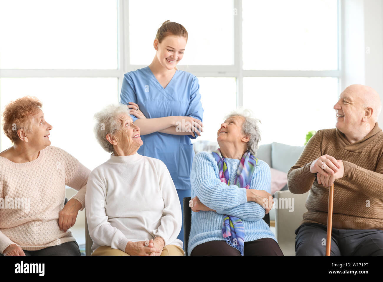 Young Caregiver With Group Of Senior People In Nursing Home Stock Photo Alamy