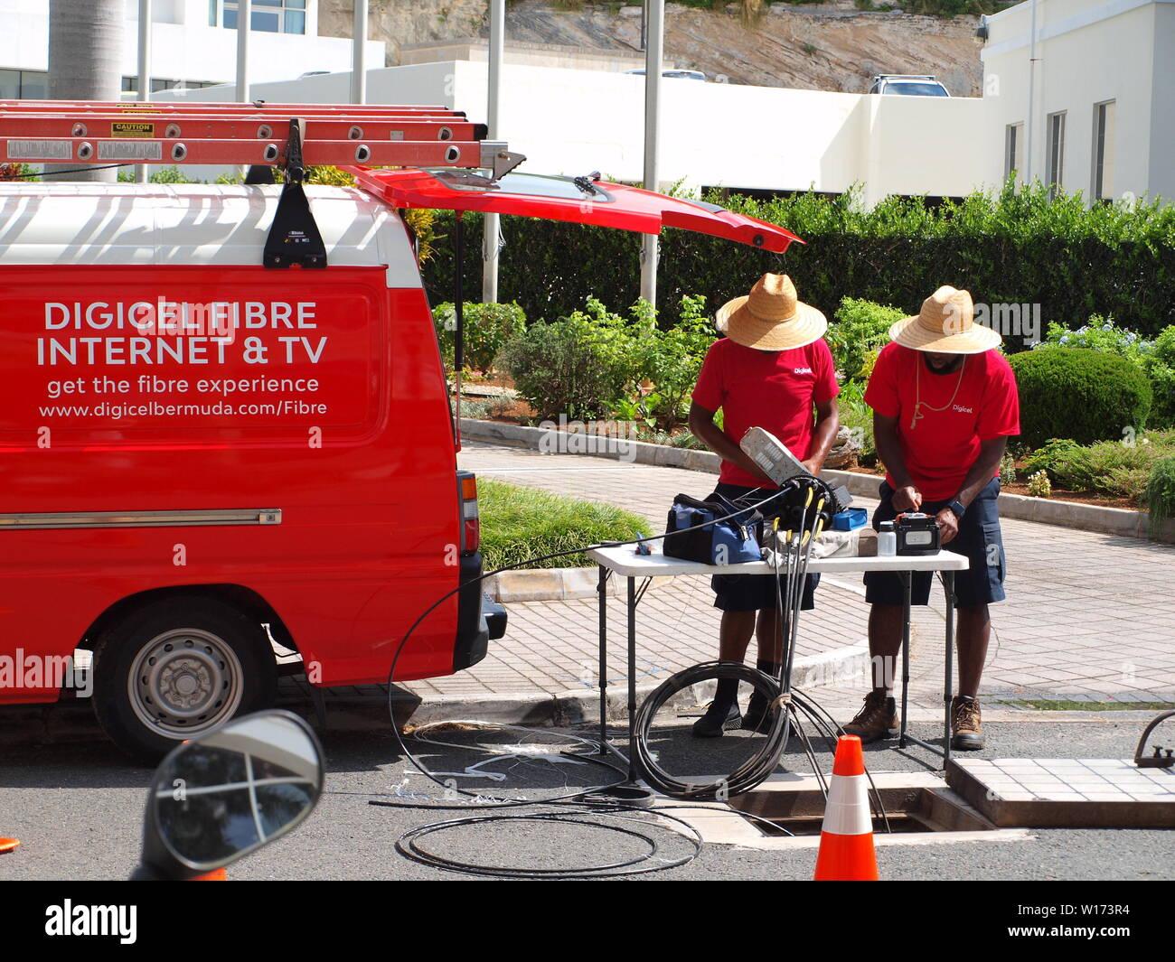 Local Bermuda utility workers in straw hats repairing fiber optic cable in Hamilton, Bermuda. Stock Photo