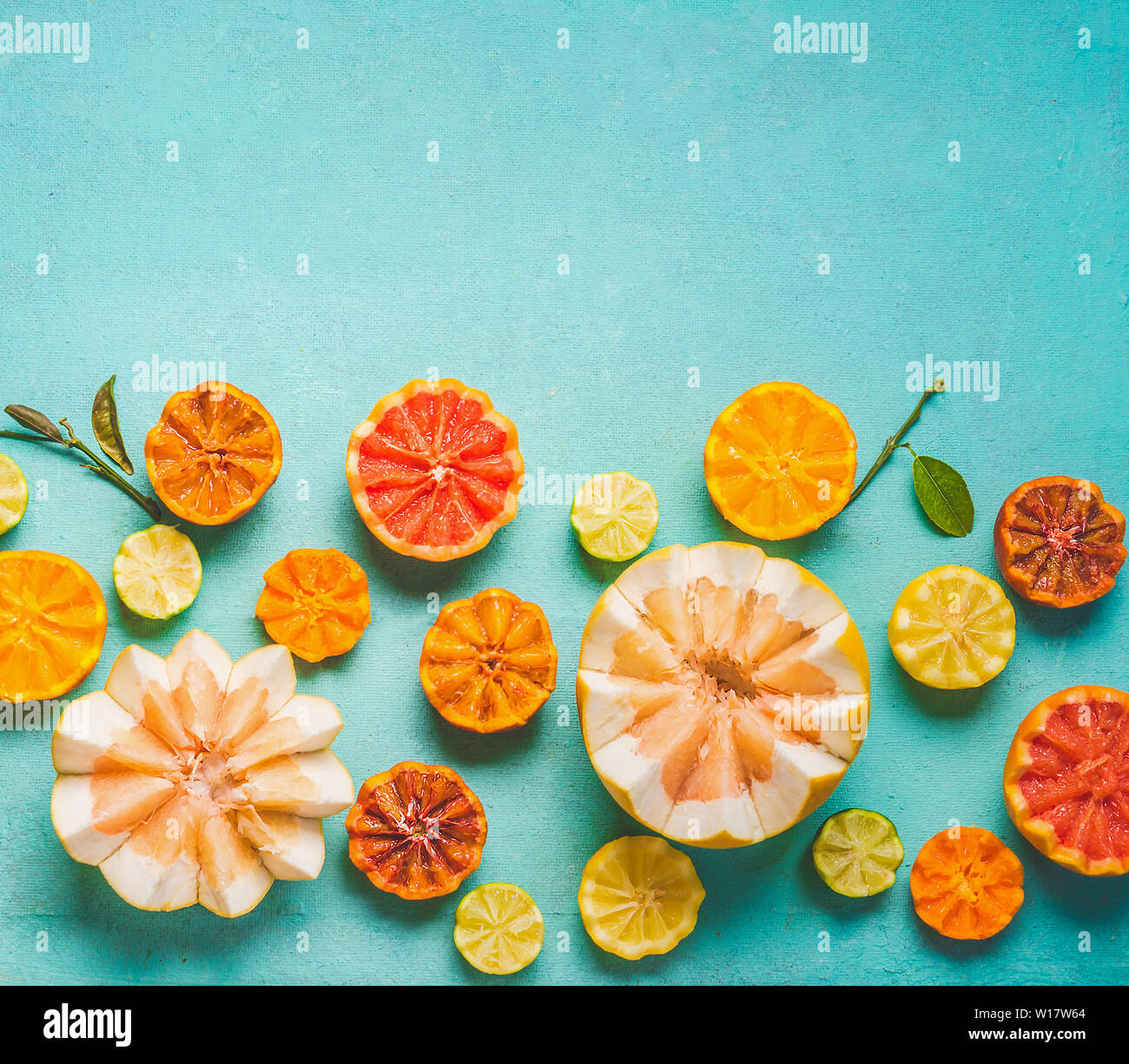 Various colorful citrus fruits halves with green leaves on light blue background, top view, border with copy space for your design. Flat lay. Healthy Stock Photo