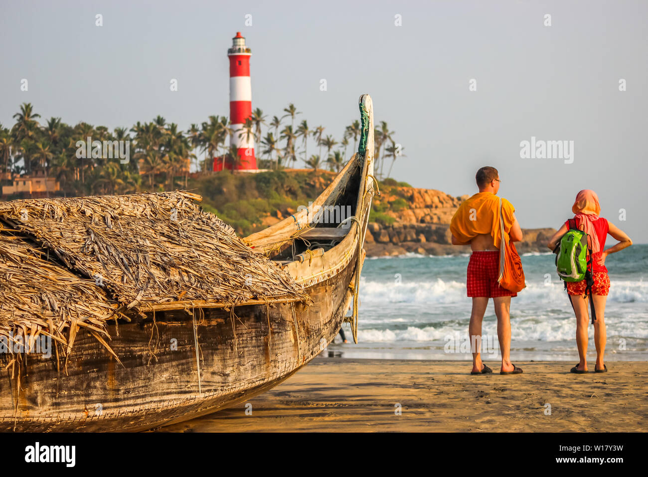 Kerala, India: Dated-June 14, 2019: A beach in Kerala Goa with a lighthouse in the background and a traditional fishing boat in the foreground. Foreig Stock Photo