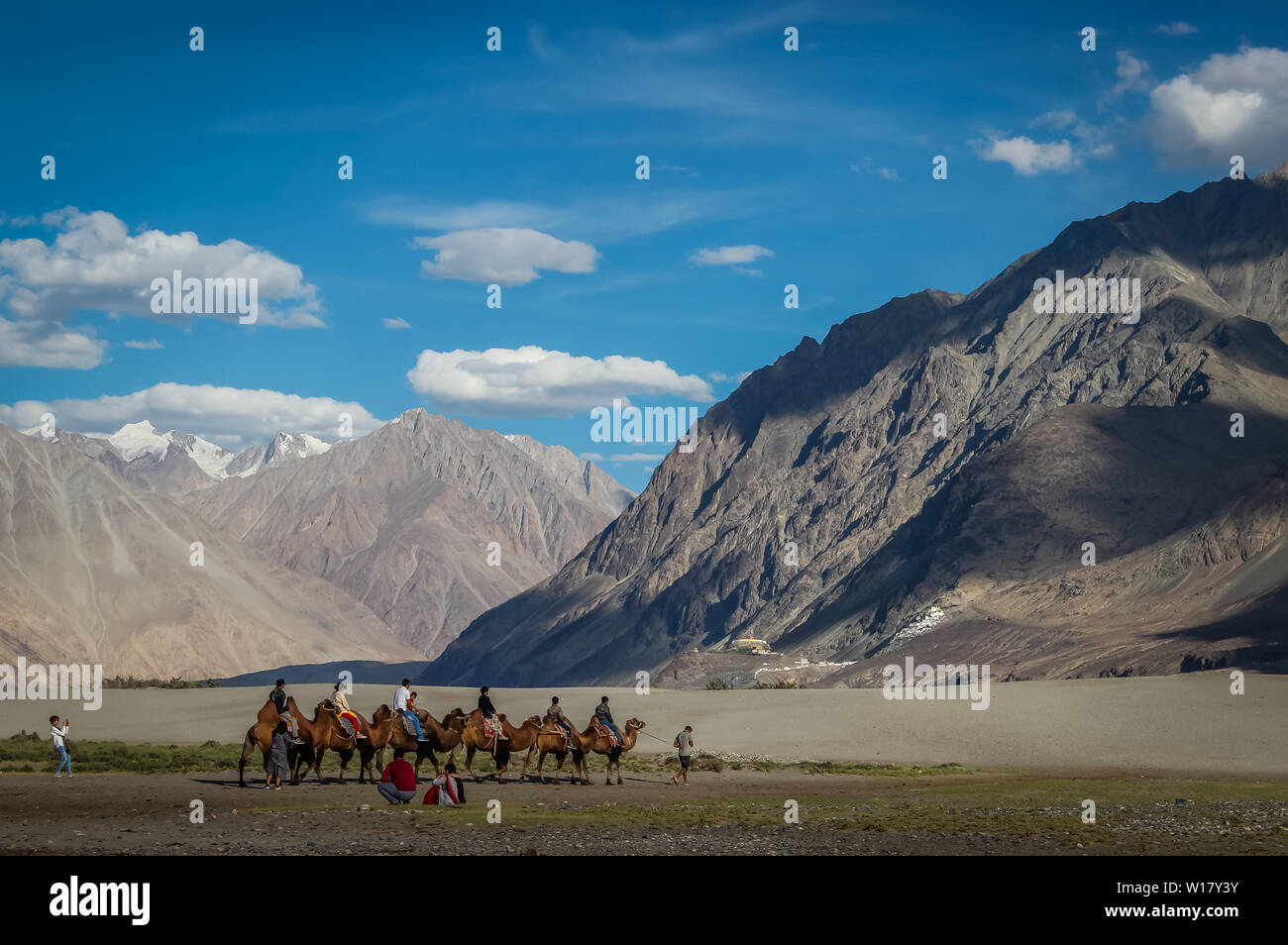 Ladakh, India; Dated- May 14, 2019: Tourists enjoying camel ride in the cold desert of Ladakh. Ladakh landscape with desert mountains and blue sky - Stock Image
