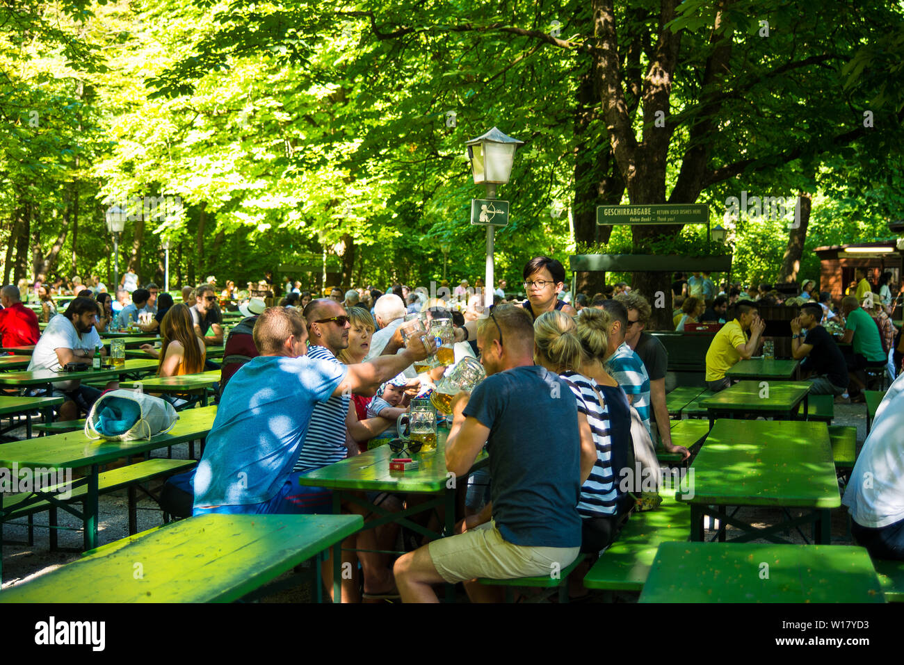 Munich,Germany-June 28,2019: A group of friends toast at a biergarten - Stock Image