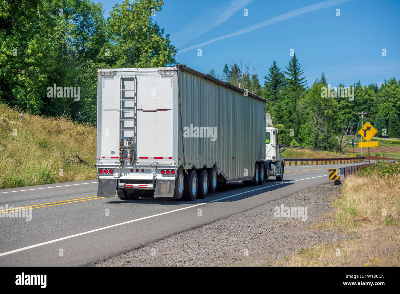 Big rig white day cab semi truck with roof spoiler transporting huge covered bulk semi trailer with ladder on the back wall moving on the turning wind Stock Photo