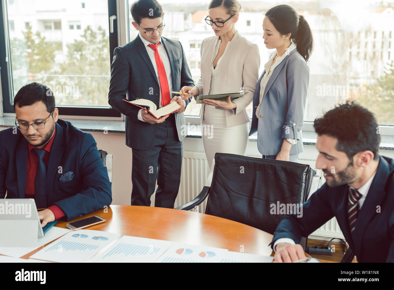 Very international consultants working on a project together - Stock Image