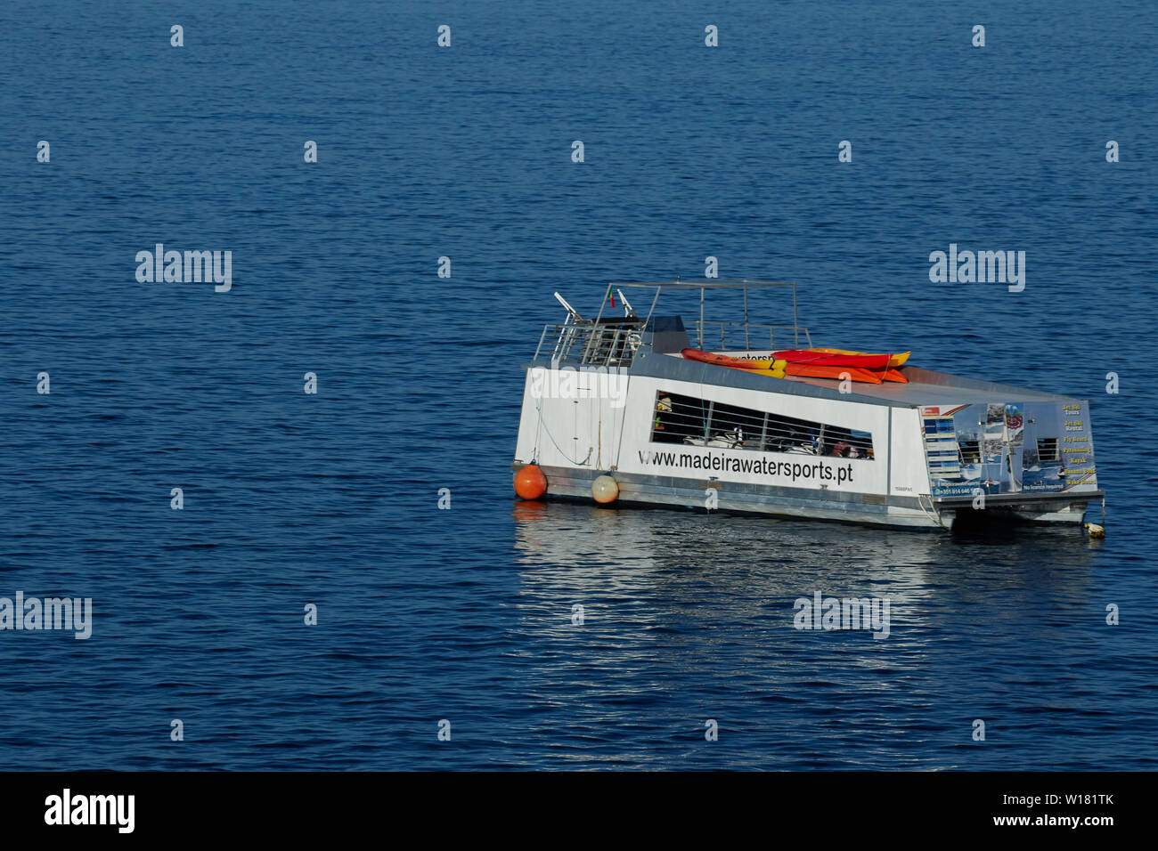 Pleasure boat moored in the North Atlantic Ocean off the coast of Madeira in the early morning before holidaymakers arrive. - Stock Image