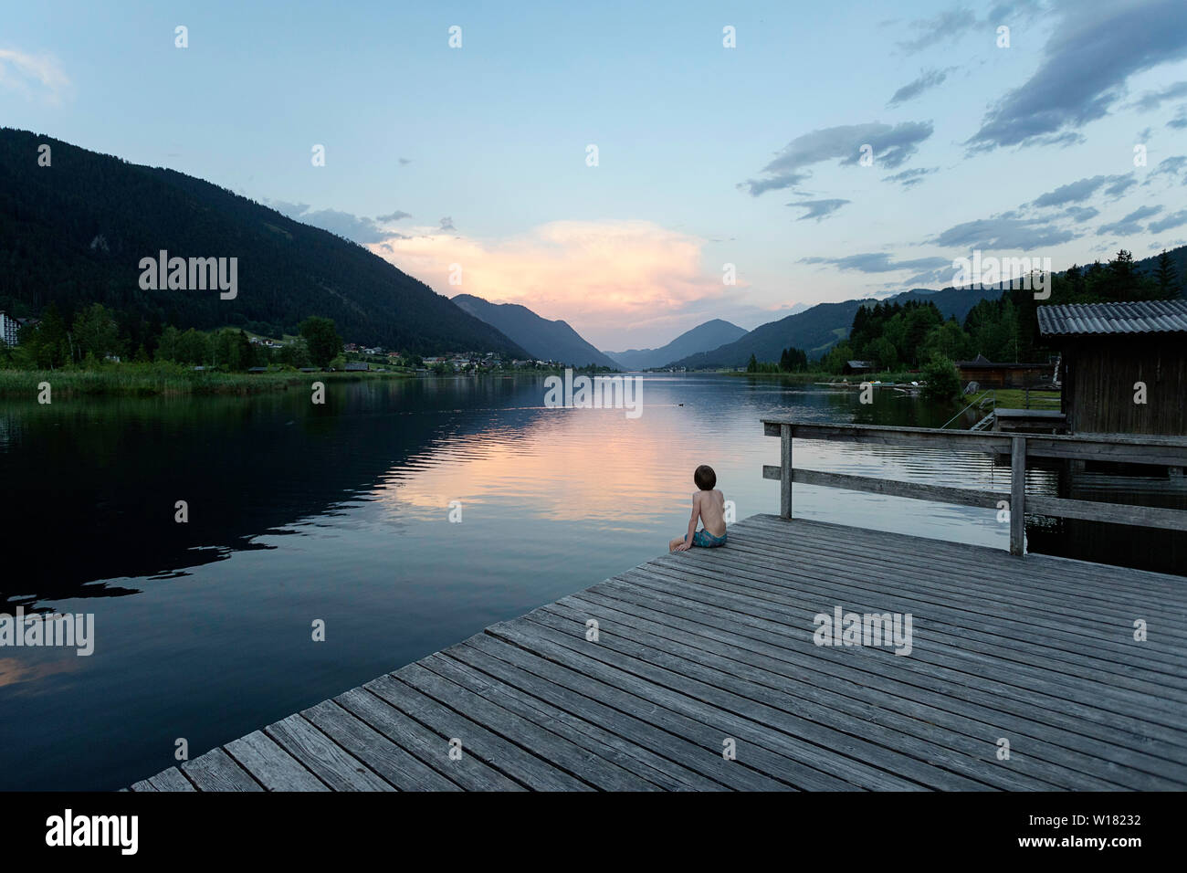 Young boy in swimming suit sitting on wooden pier on lake Weissensee in Austria at sunset - Stock Image