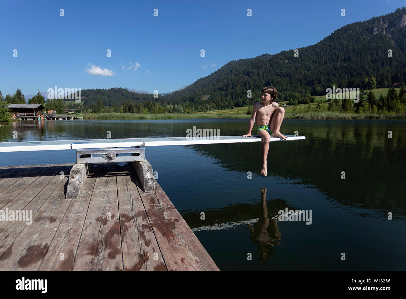 Young boy in swimming suit sitting on diving board on lake Weissensee in Austria - Stock Image