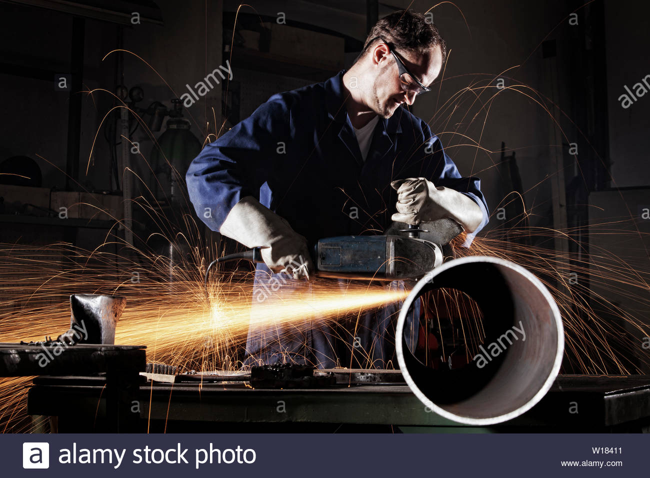 Heavy industry worker cutting steel pipe with angle grinder in workshop. - Stock Image