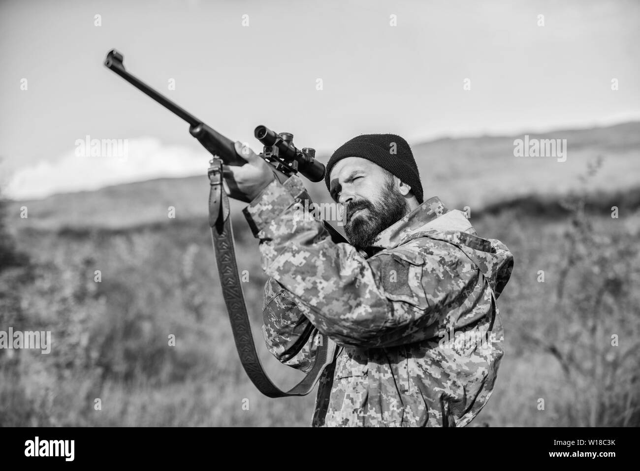 Aiming skills. On my target. Bearded hunter spend leisure hunting. Hunting optics equipment for professionals. Brutal masculine hobby. Man aiming target nature background. Hunter hold rifle aiming. - Stock Image
