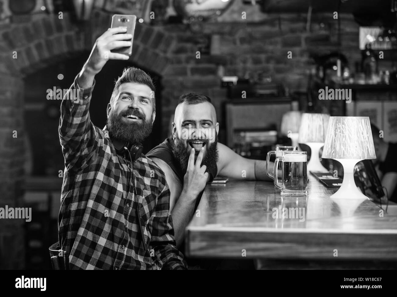 Send selfie to friends social networks. Man in bar drinking beer. Take selfie photo to remember great evening in pub. Online communication. Man bearded hipster hold smartphone. Taking selfie concept. - Stock Image