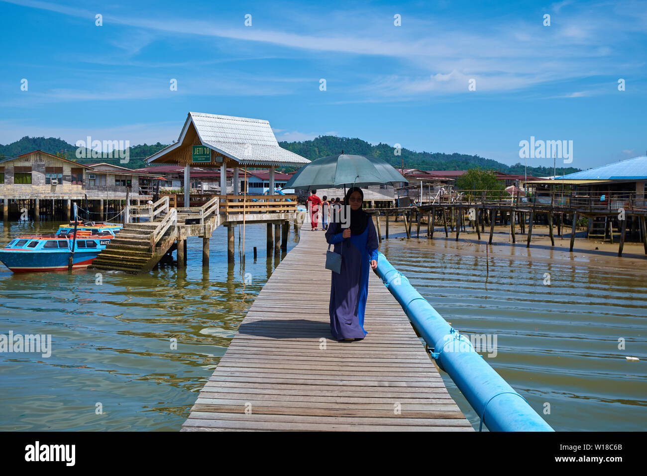 People wallking along one of the main wood paths leading into the water stilt village Kampong Ayer in Bandar Seri Begawan,Brunei. - Stock Image
