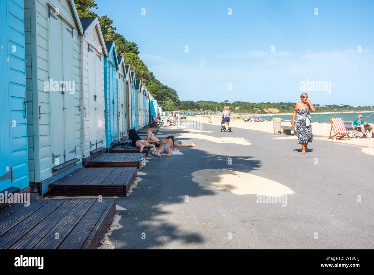 Row of beach huts in different pastel blue shades run along the top of Avon Beach at Mudeford, Christchurch in Dorset, UK. A sandy beach with pebbles. Stock Photo