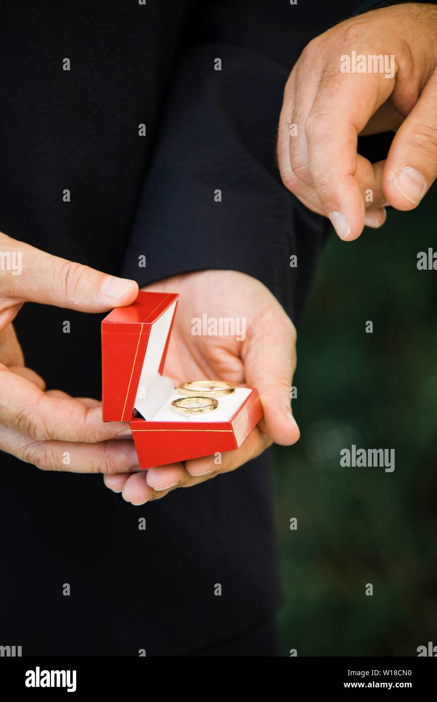 Man's hand going to take wedding ring from red box, wedding ceremony moment - Stock Image