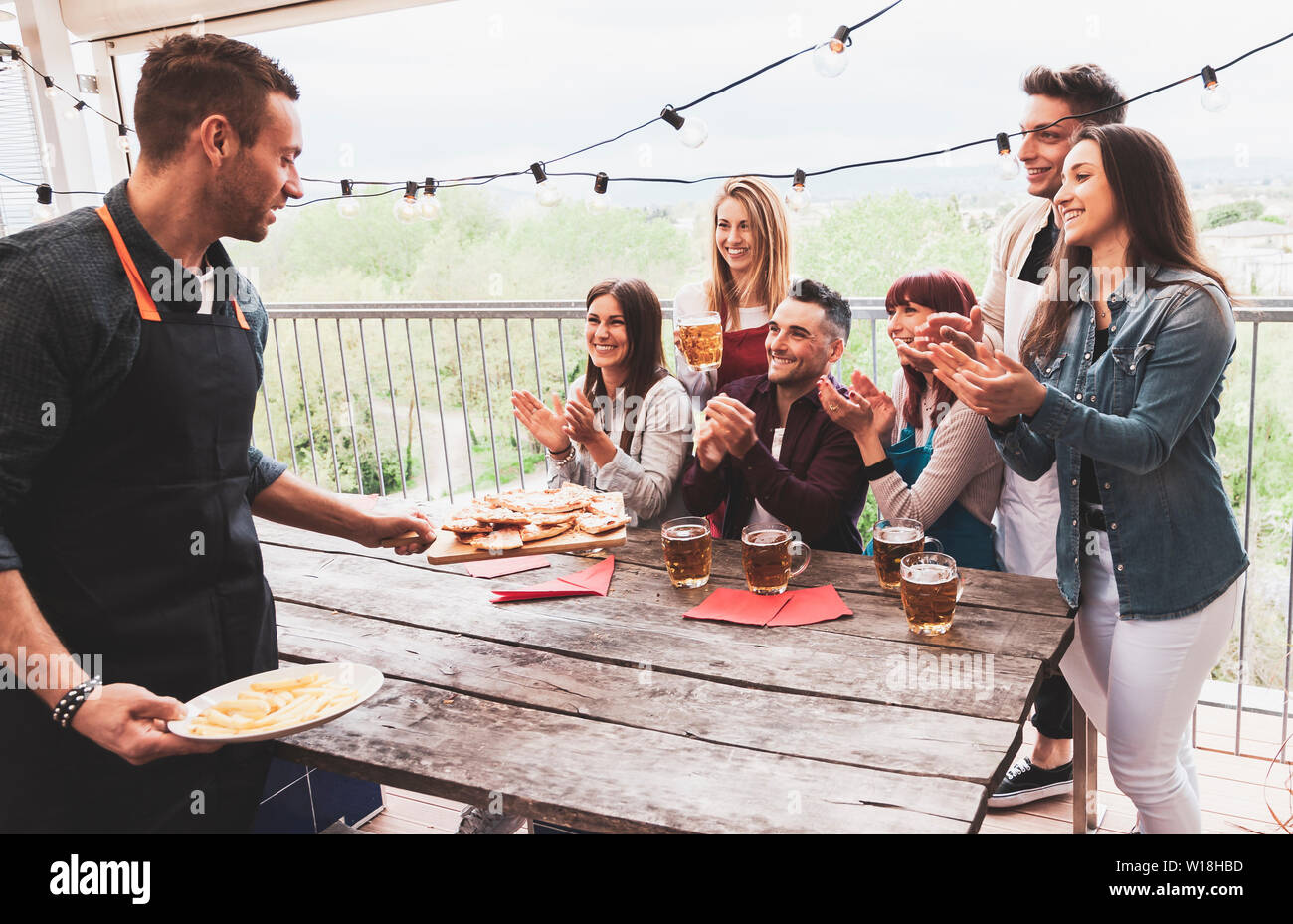 Happy group of friends drinking beer and eating pizza at brewery bar restaurant. concept with young people having genuine fun Stock Photo