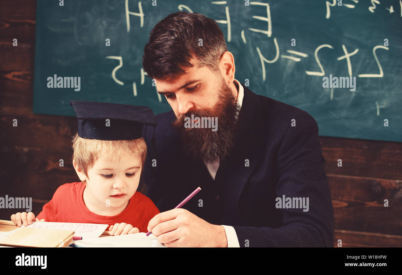 Homeschooling concept. Teacher in formal wear and pupil in mortarboard in classroom, chalkboard on background. Father checking homework, helps to boy, son. Enthusiastic kid studying with teacher. - Stock Image