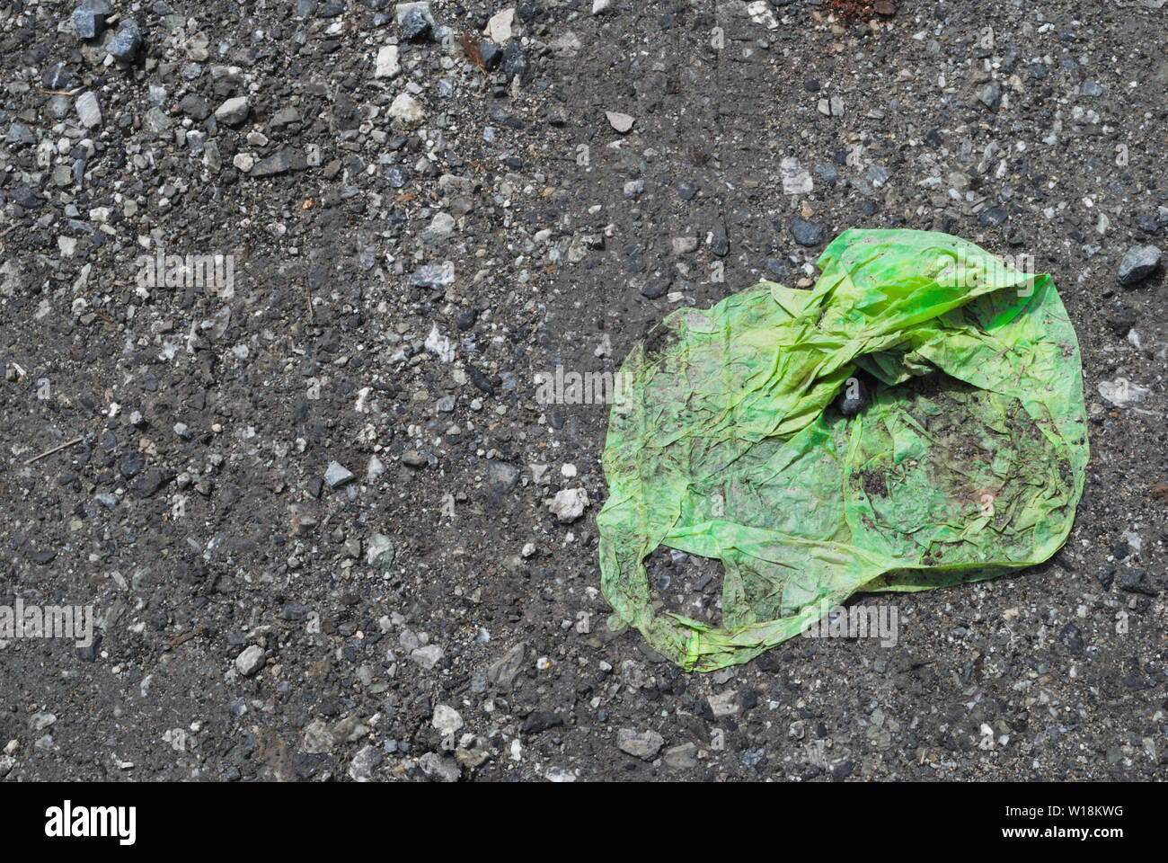 The green plastic bag was blown to the parking lot and was hit by a car. - Stock Image