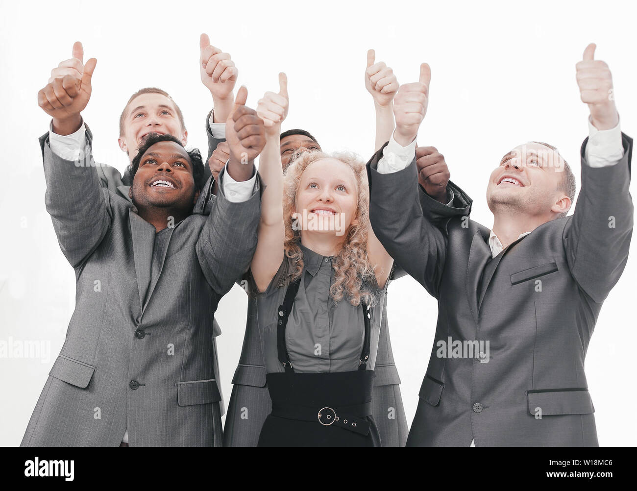 closeup.international business team showing thumbs up and looking at copy space - Stock Image