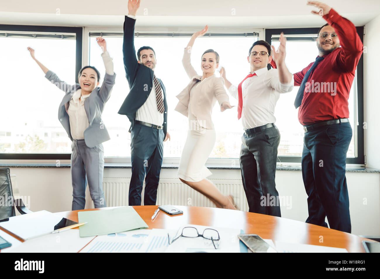 Diversity team of business people jumping high in the office  - Stock Image