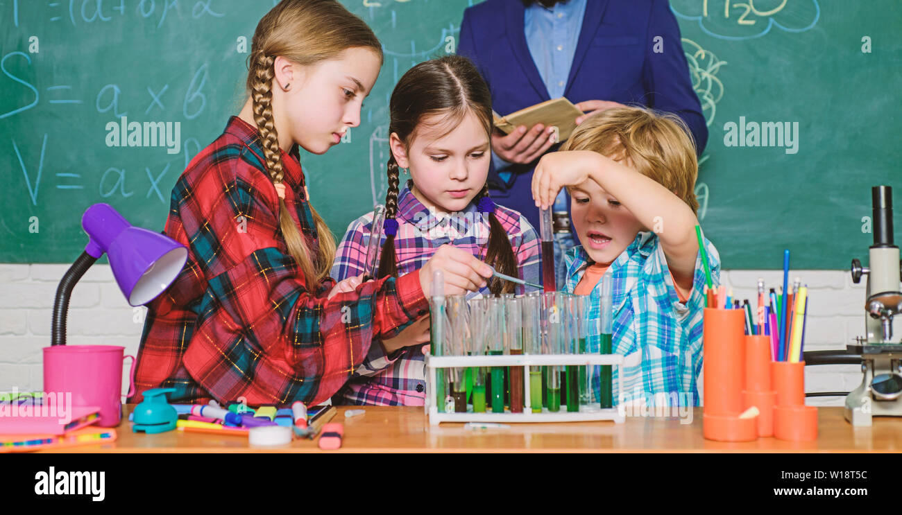 back to school. kids in lab coat learning chemistry in school laboratory. chemistry lab. making experiment in lab or chemical cabinet. happy children teacher. Hard to diagnose. - Stock Image