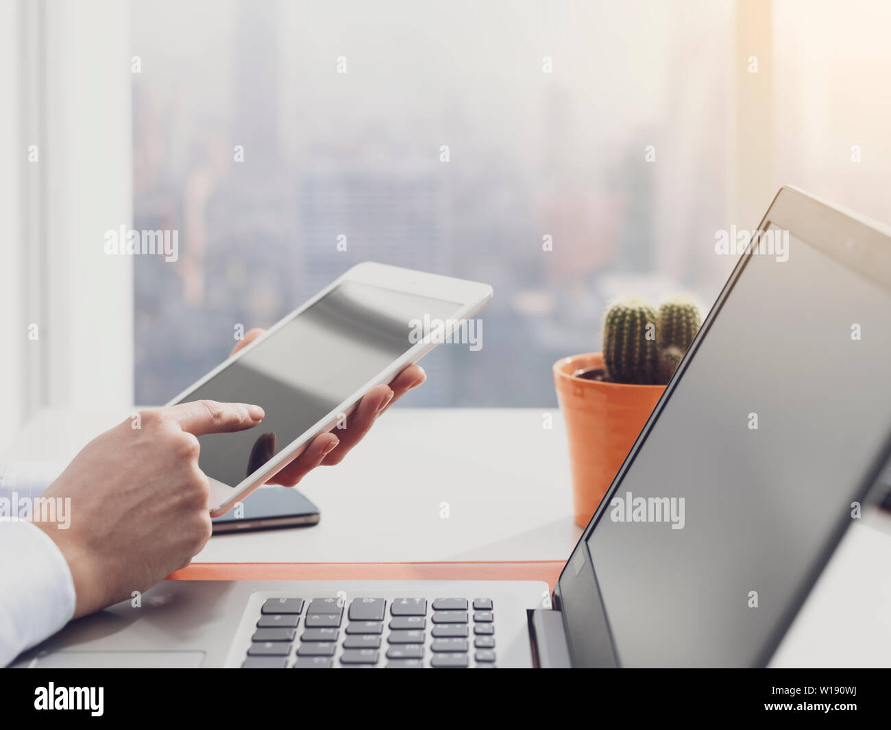 Corporate businesswoman sitting at desk in her office and working with a digital touch screen tablet - Stock Image