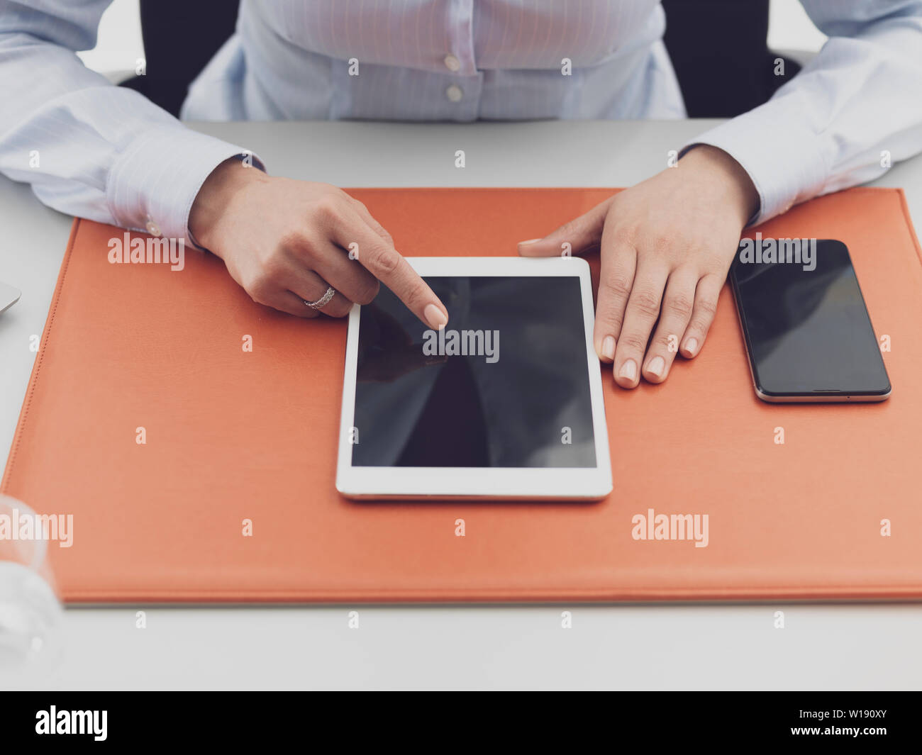 Female office worker sitting at desk and working with a digital touch screen tablet - Stock Image