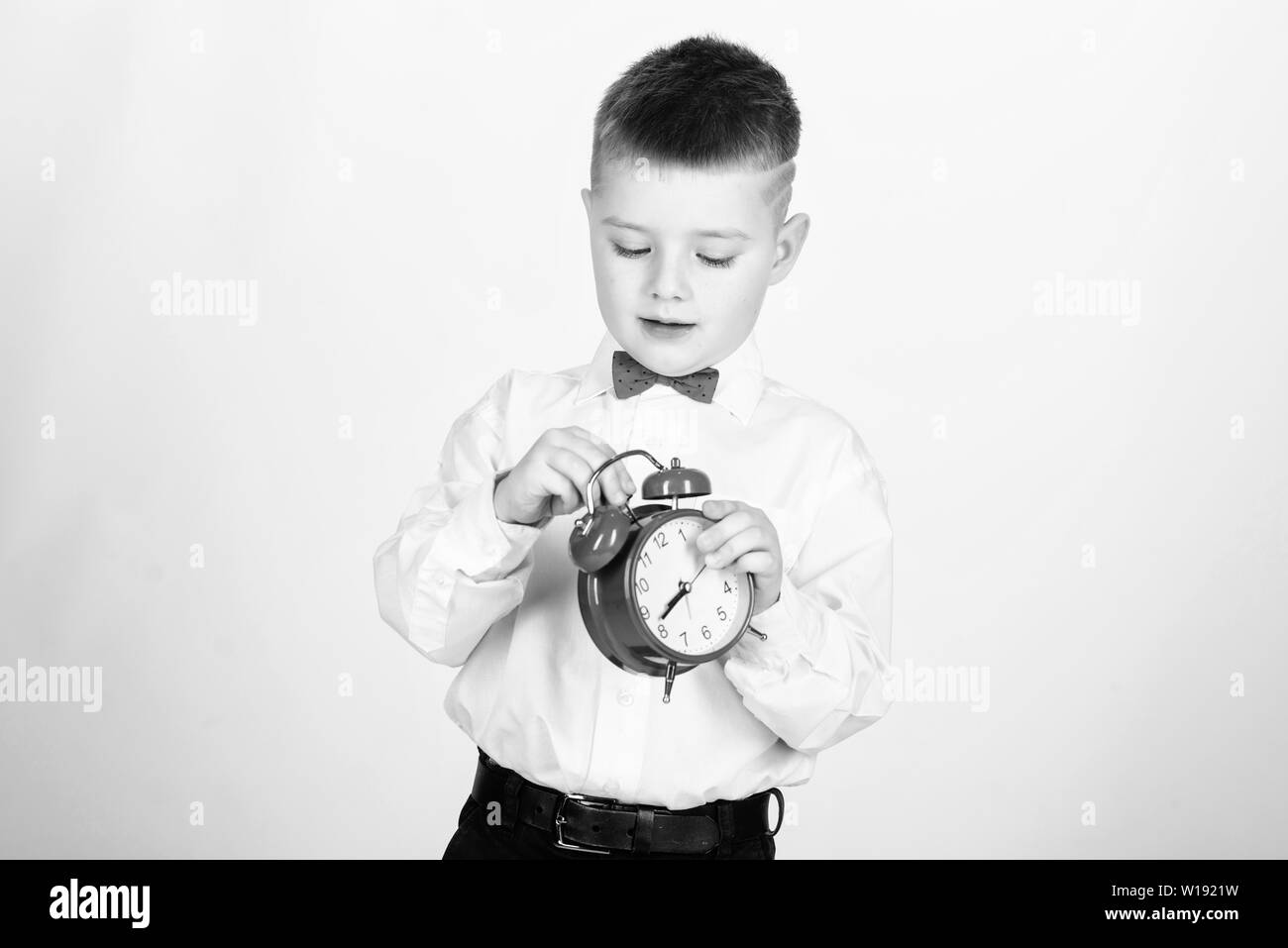 Time management. Morning. little boy with alarm clock. Time to relax. happy child with retro clock in bow tie. tuxedo kid. Happy childhood. Party time. Businessman. Formal wear. Starting day. - Stock Image
