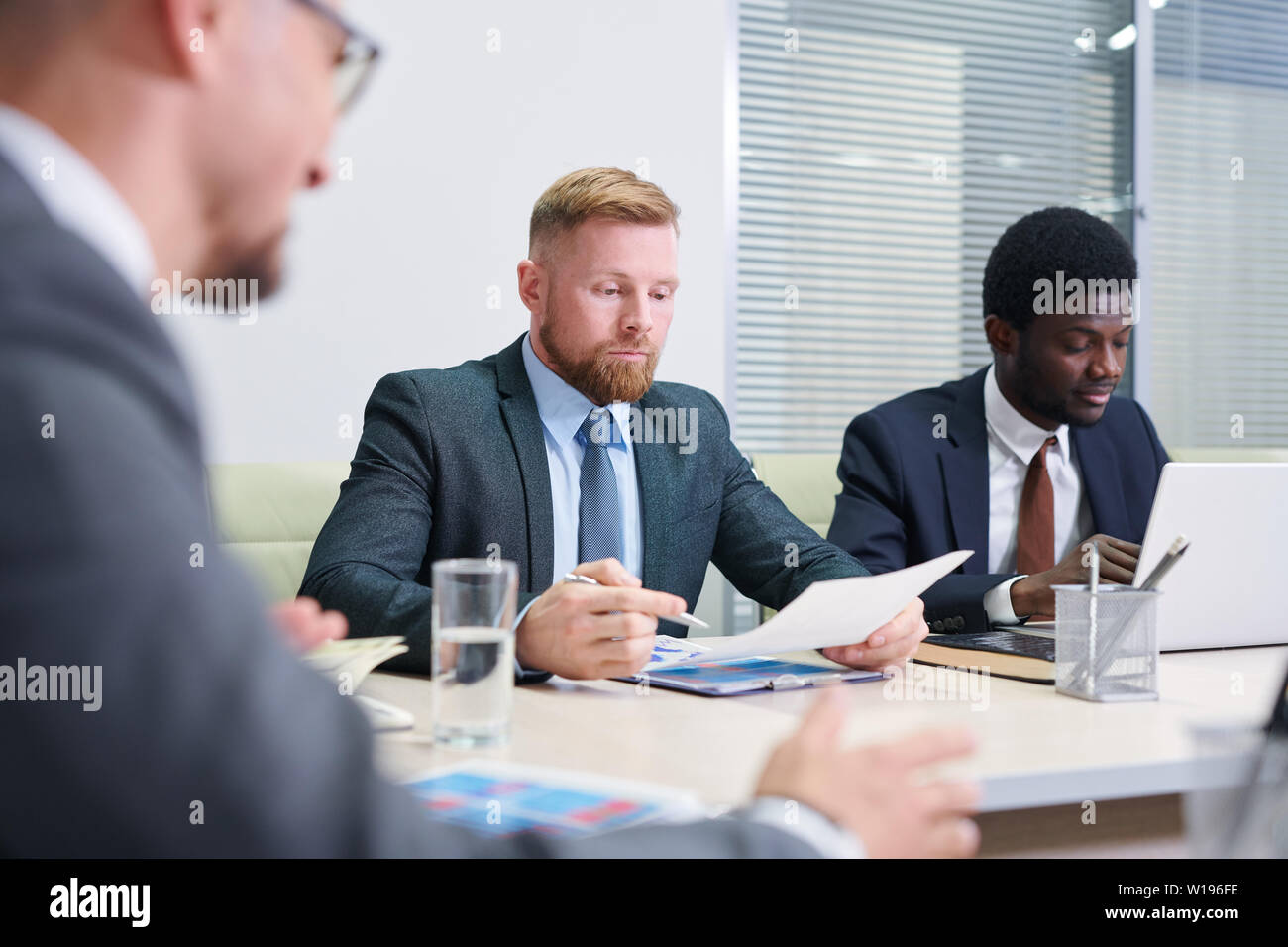 Group of young multicultural co-workers getting ready with reports before conference - Stock Image