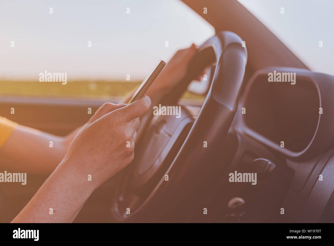 Dangerous texting while driving behavior, close up of female hands using mobile phone and operating motor vehicle on road through countryside, selecti Stock Photo