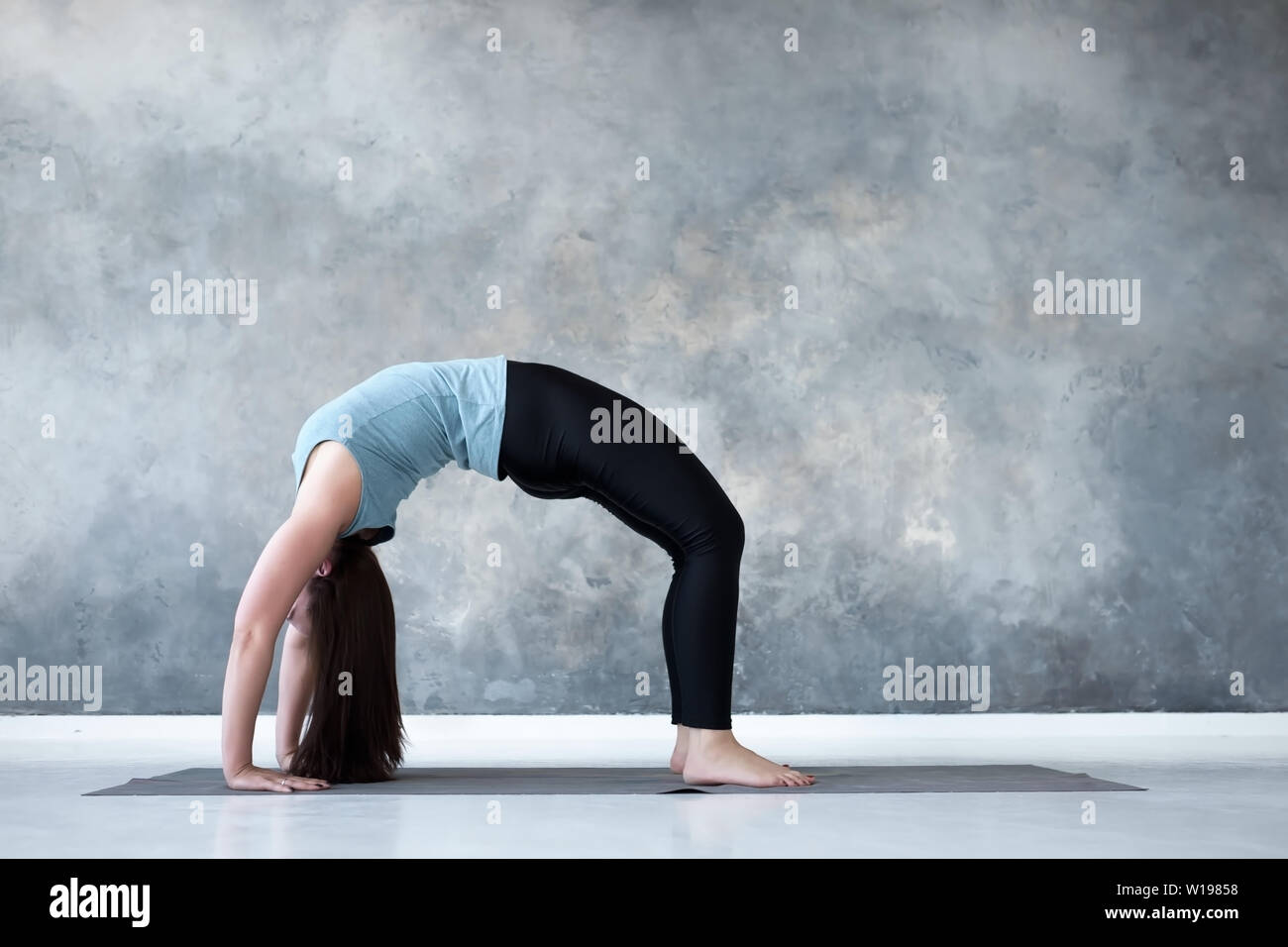 Woman practicing yoga, standing in Urdhva Dhanurasana pose - Stock Image
