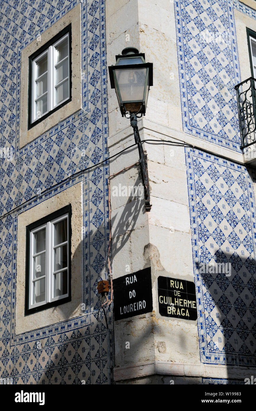Vertical view of historic gas lamp on blue tiled building on corner and Portuguese  street signs in Alfama Lisbon Portugal Europe  KATHY DEWITT Stock Photo