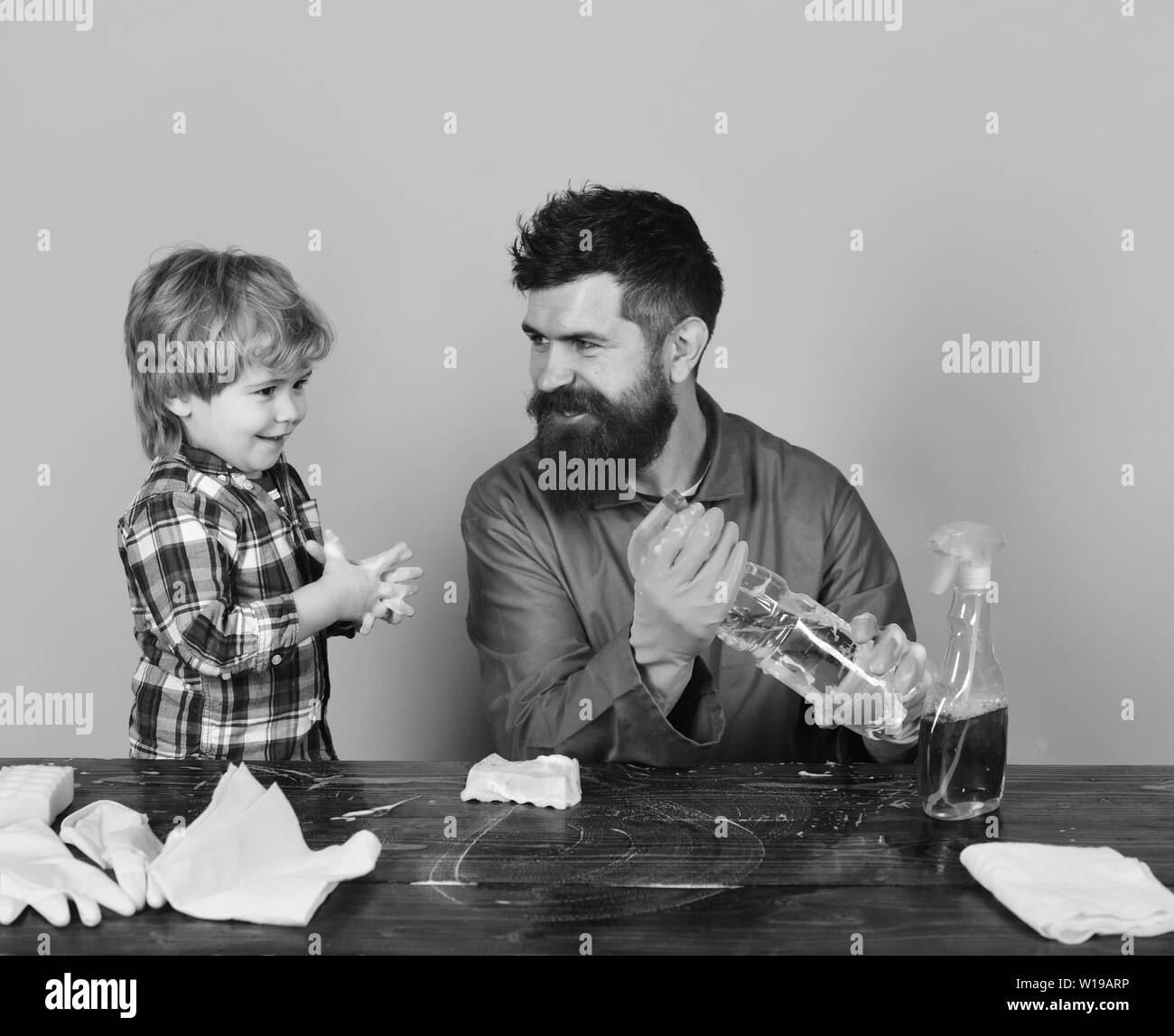 Guy with beard and mustache with rubber gloves holds spray. Fatherhood concept. Man with smile and child at wooden table on pink background. Father and son plays with cleaning props. - Stock Image