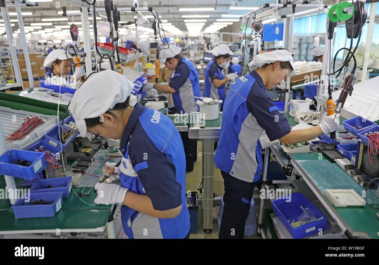 (190701) -- DALIAN, July 1, 2019 (Xinhua) -- Workers are seen at a workshop of OMRON Dalian Co., Ltd. in Dalian, northeast China's Liaoning Province, March 21, 2019. The 2019 Summer Davos Forum is held from July 1-3 in northeast China's coastal city of Dalian. Established by the World Economic Forum in 2007, the forum is held annually in China, alternating between the two port cities of Dalian and Tianjin. Summer Davos has been reshaping the landscape of Dalian's regional economy and strengthening the port's trade with other markets. Dalian has become an international city and a showpiece of C - Stock Image
