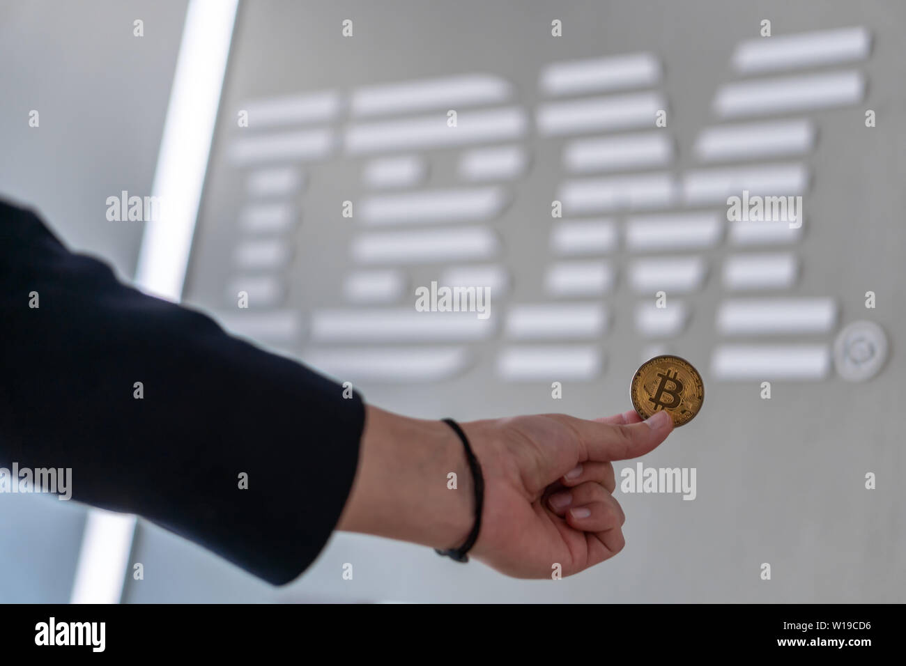 Businessman holding Bitcoin coin with the IBM logo on a laptop screen, Slovenia - February 26th, 2019 Stock Photo