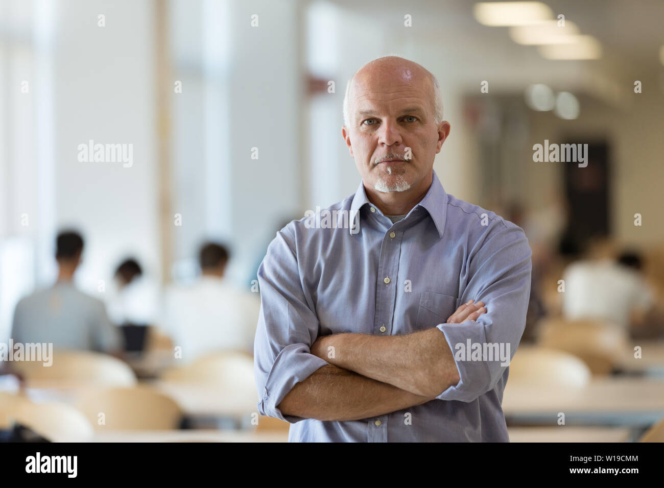 Resolute senior businessman standing with folded arms and a serious stern expression in a large open plan office with people working in the background - Stock Image