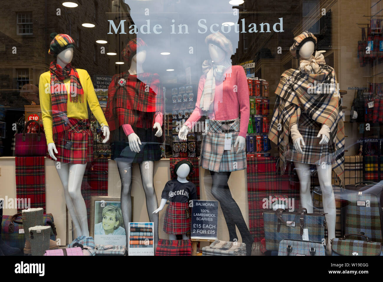 Tartan kilts and national Scots fabrics on sale in the window of a tourist shop on the Royal Mile in Edinburgh, on 25th June 2019, in Edinburgh, Scotland. - Stock Image