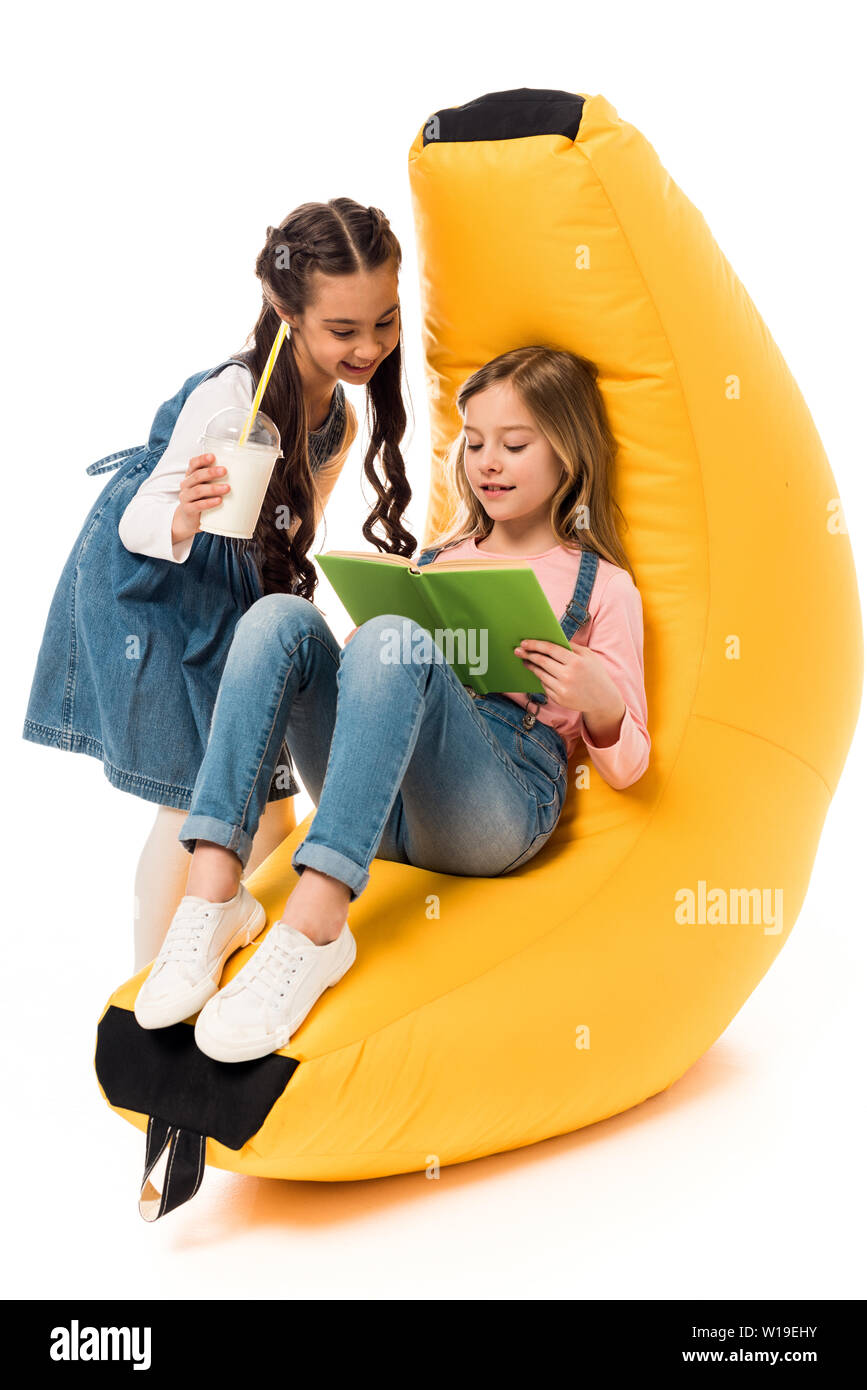 Swell Two Smiling Kids With Bean Bag Chair Reading Book On White Cjindustries Chair Design For Home Cjindustriesco