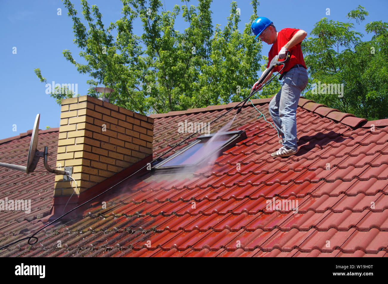 House roof cleaning with pressure tool  Worker on top of