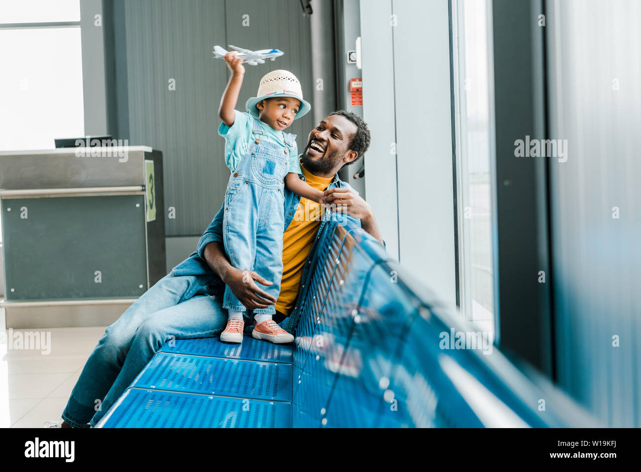happy african american father looking at son while boy playing with toy plane in airport Stock Photo
