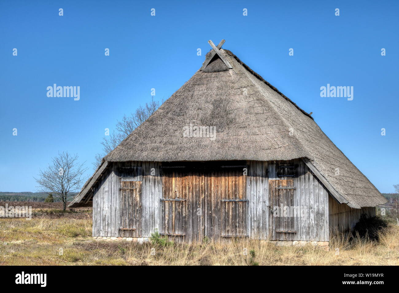 Typical thatched sheepfold in the nature reserve Lueneburg Heath which offers space for 350 sheep. Each flock of sheep has two of these stables. - Stock Image