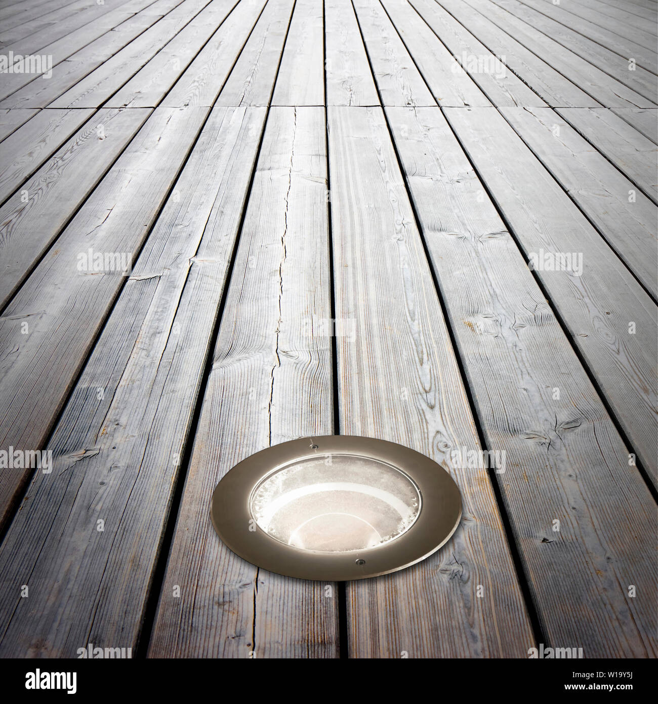 Recessed floor lamp on old wooden floor - image with copy space - Stock Image